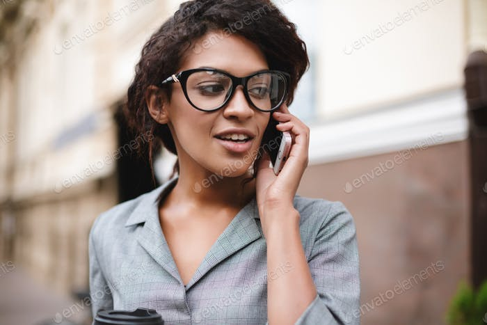 Beautiful African American girl in glasses standing on street and talking on her cellphone
