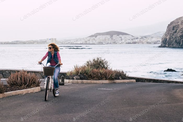 Woman ride the bike outdoor with coast ocean view - healthy transport lifestyle green environment