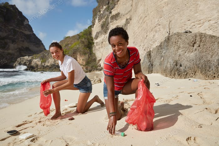 Campaign for cleaning our environment. Happy diverse women pick up plastic bottles, fight against en
