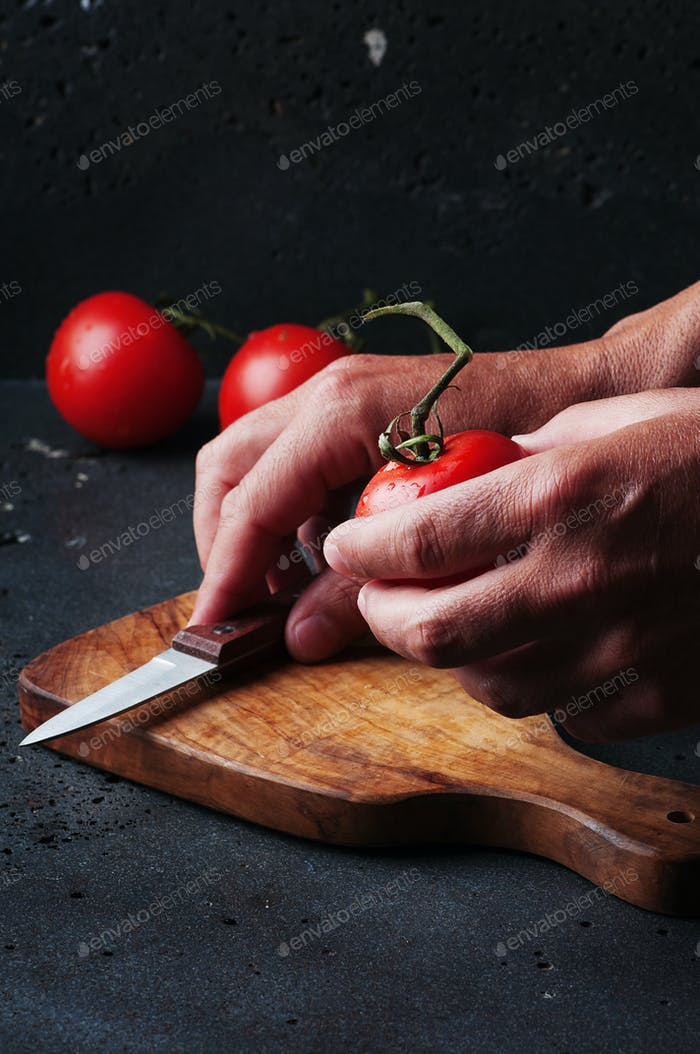 Man's hands cutting a tomato