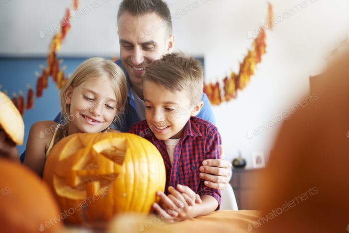 Father and offsprings over halloween pumpkin