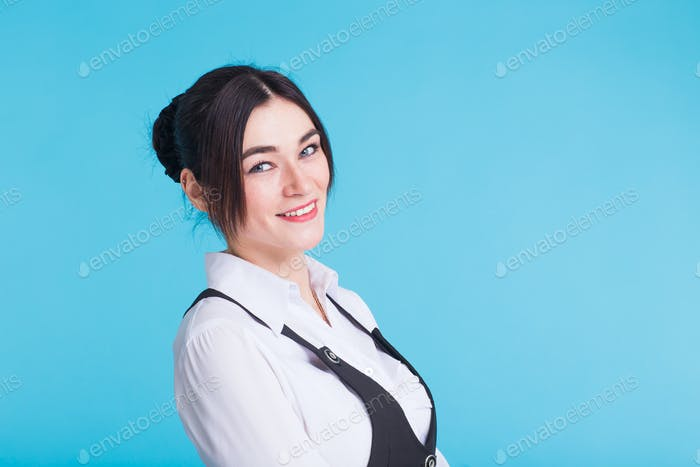 Pretty young smiling brunette woman in waistcoat looking at camera on blue background.