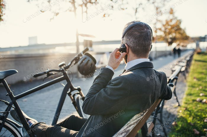 Businessman commuter with bicycle sitting on bench in city, listening to music.