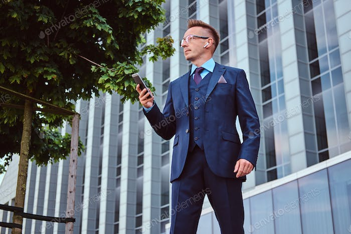 Confident businessman dressed in an elegant suit standing outdoors against cityscape background.