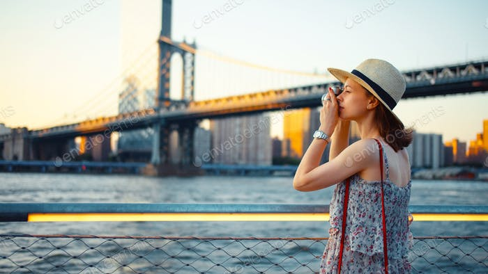 Mujer joven con una cámara retro en el puente de Manhattan
