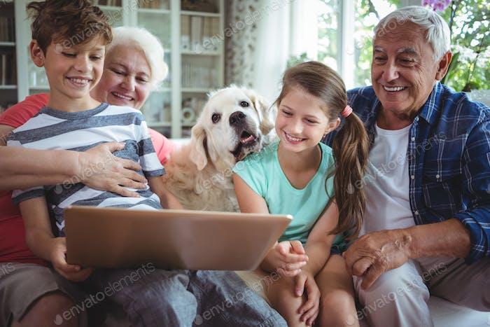 Großeltern und Enkelkinder mit Laptop im Wohnzimmer