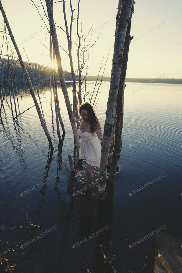 A woman in a white dress or nightdress in shallow water at dusk