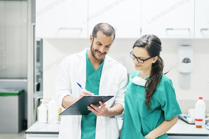 Doctor and nurse examining report of patient