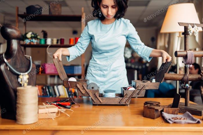 Needlework, female master at workplace in workshop