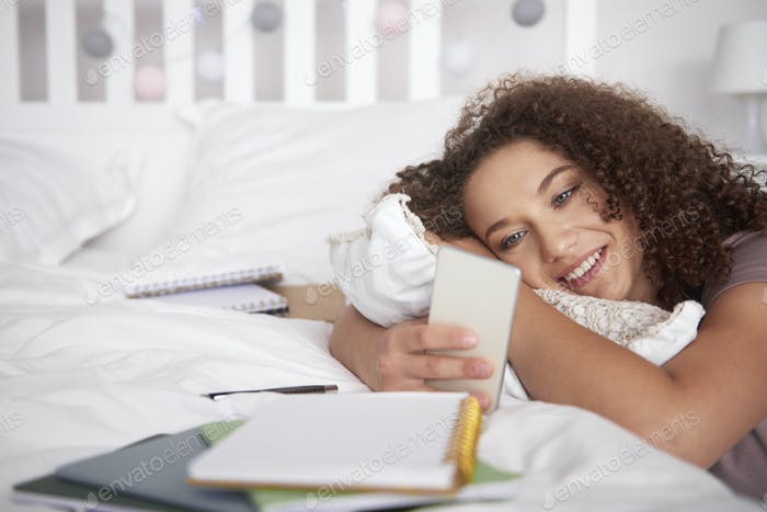 Lächeln Teenager-Mädchen mit einem Smartphone in Ihr Zimmer