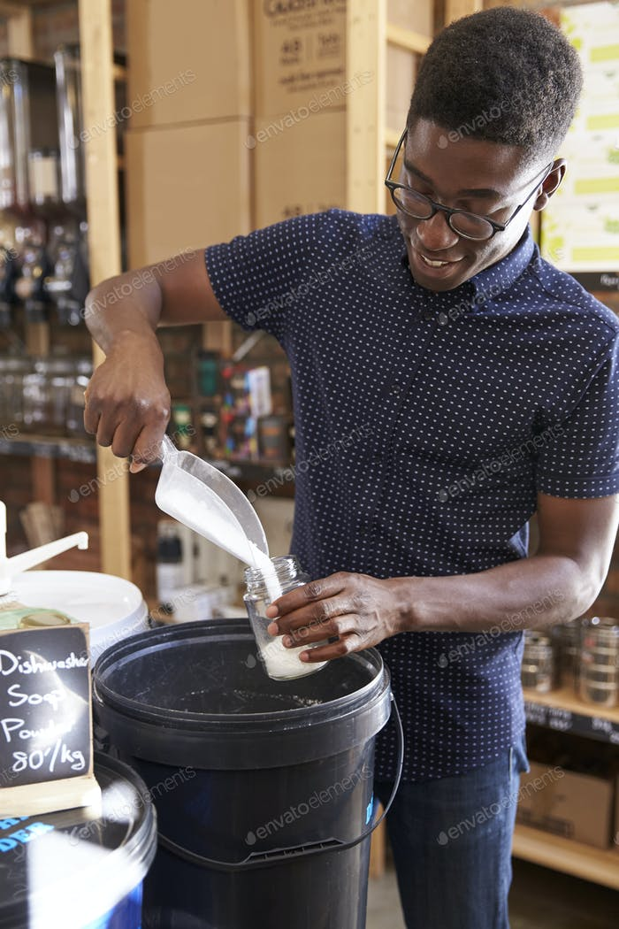 Man Filling Container With Dishwasher Powder In Plastic Free Grocery Store