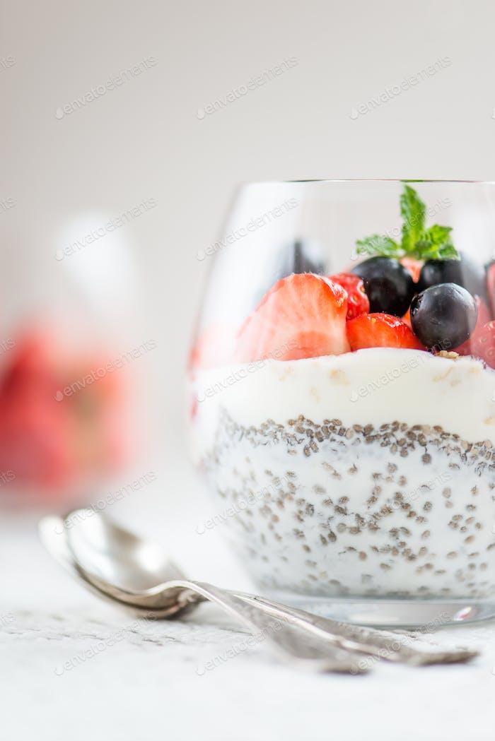 chia seeds in yogurt with granola, yogurt and strawberries, blueberries and mint