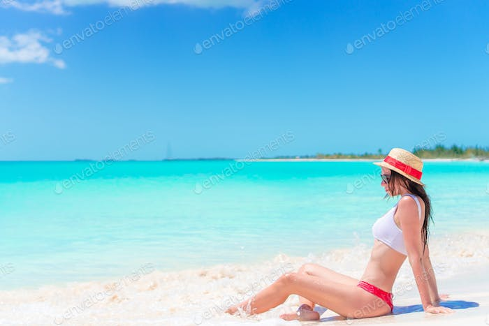 Young woman on a tropical beach with hat