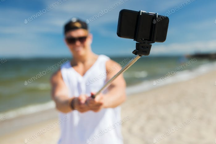 man with smartphone taking selfie on summer beach