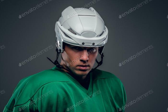 Portrait of hockey player on grey background.