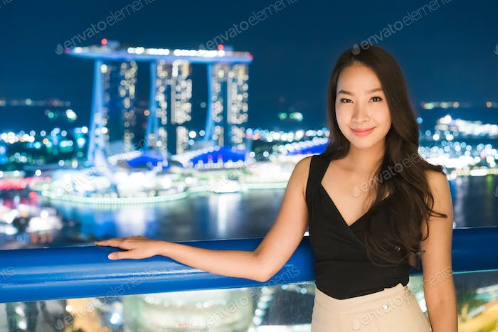 Beautiful Asian women smile and happy with singapore city view