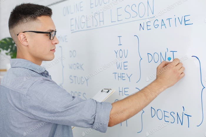 Online school and teacher during quarantine. Serious man in glasses writes rules of english on white