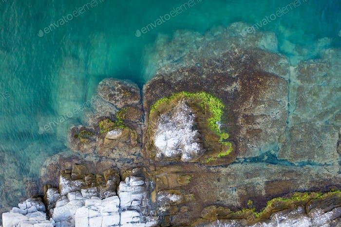 Luftdrohnenansicht einer abgelegenen felsigen Insel im offenen Meer.