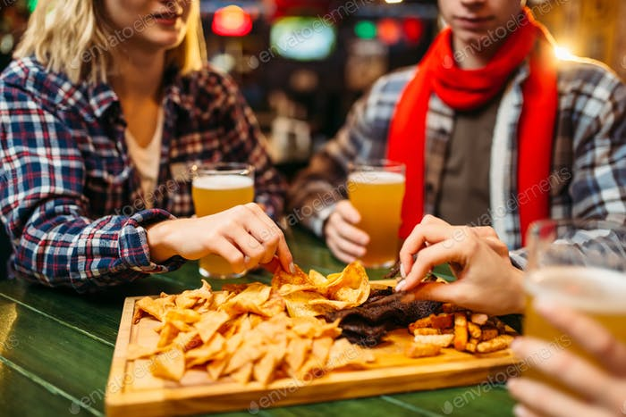 Fans drinks beer and eats chips in sports bar