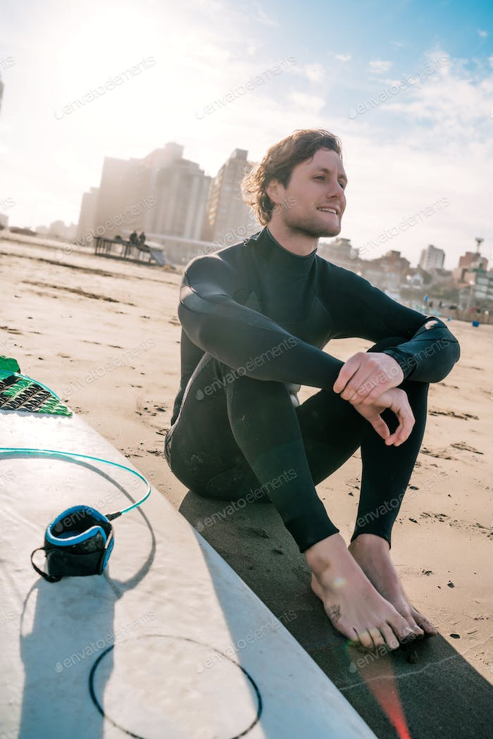 Surfer sitting on sandy beach and next to surfboard.