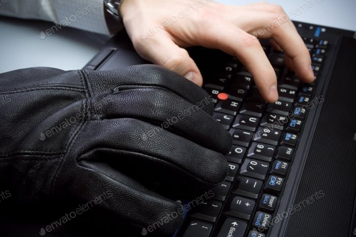 Computer theft with hands on laptop keyboard