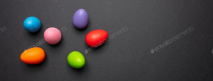 Easter eggs, pastel colors painted on dark gray background, banner