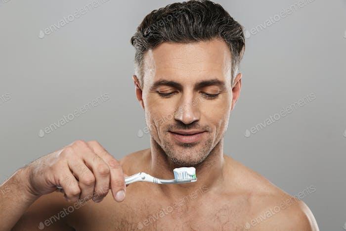 Handsome mature man brushing his teeth.