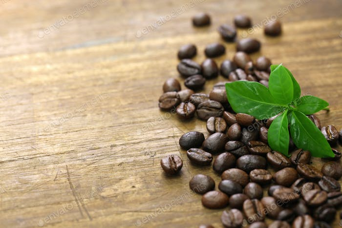 scattered roasted coffee beans and leaves on wooden background
