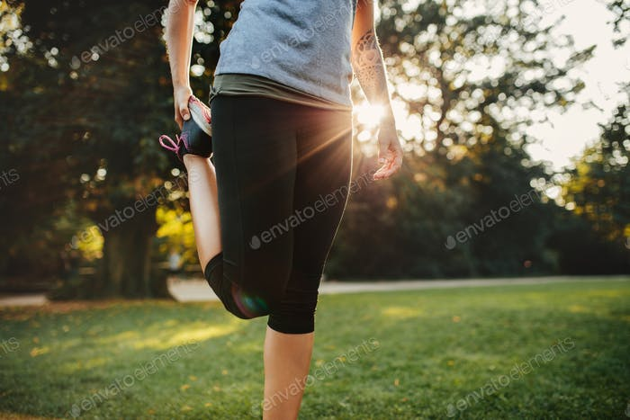 Fitness woman stretching legs in park