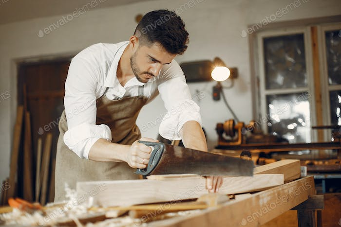 Handsome carpenter working with a wood