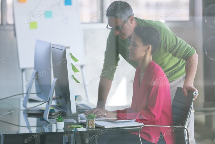 Side view of attentive Multi-ethnic business people working at desk in creative office