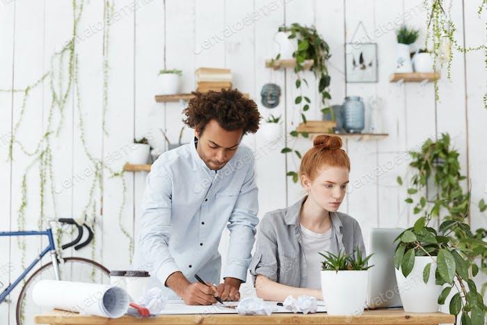 Concepto de cooperación y trabajo en equipo. Dos compañeros de trabajo de ingenieros sentados juntos en el escritorio y trabajando en
