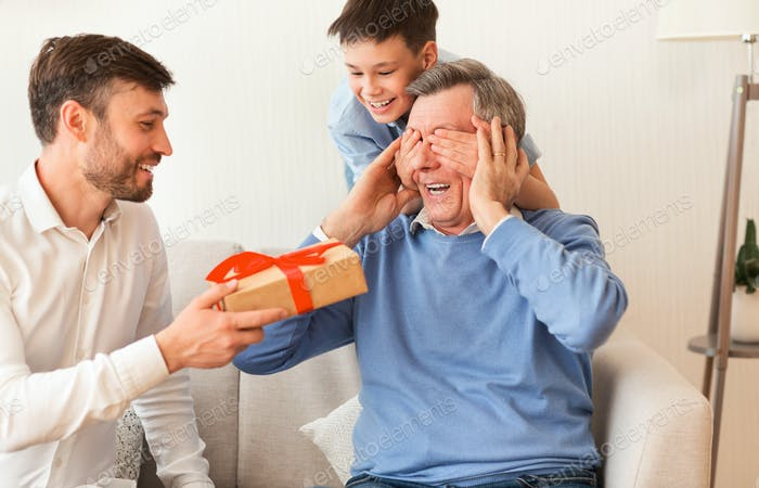 Mature Son And Grandson Congratulating Grandfather Giving Gift Box Indoor