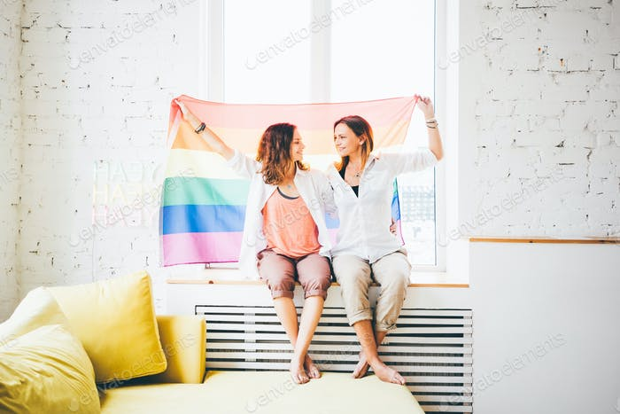 lesbian couple in love sitting near the window with the rainbow flag.