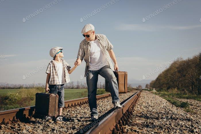 Vater und Sohn zu Fuß auf der Bahn zur Tageszeit.