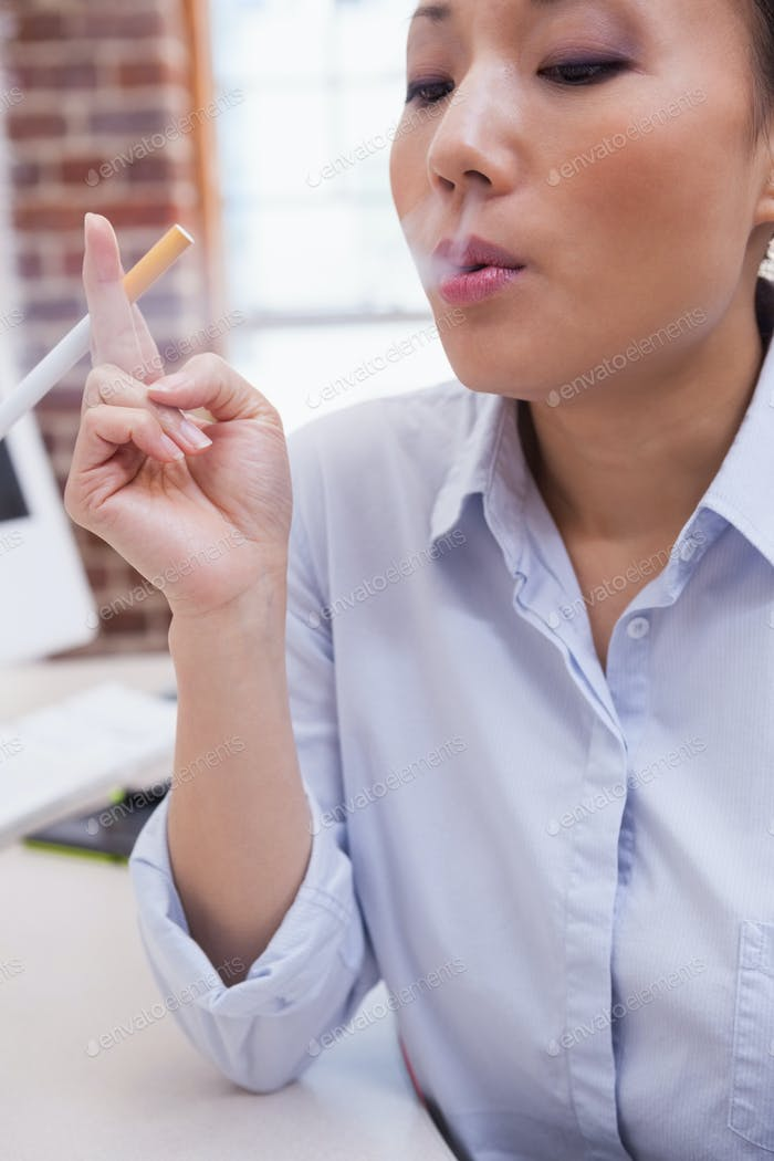 Casual businesswoman smoking an electronic cigarette in the office