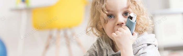 Blond little boy holding inhaler