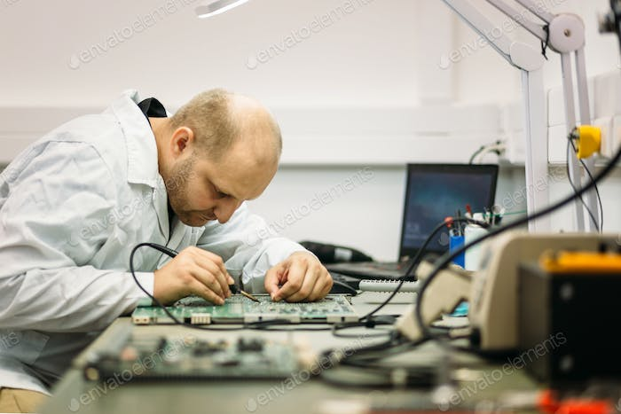 Technician fixing motherboard by soldering