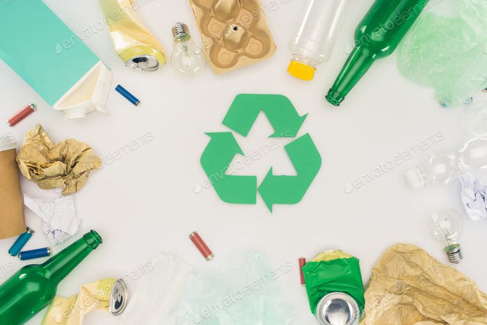 top view of various types of trash surrounding recycle sign on white