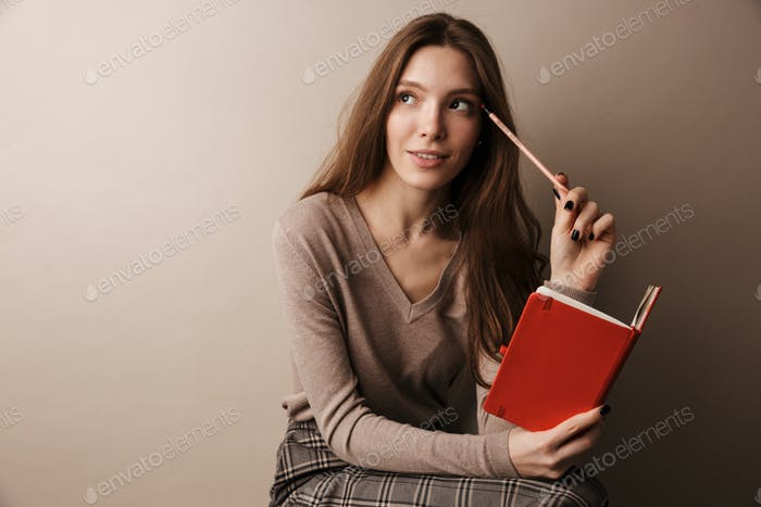 Photo of caucasian charming woman thinking and holding diary