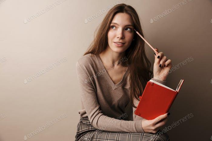Foto von kaukasischen charmanten Frau denken und halten Tagebuch
