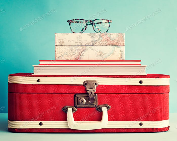 Hipster eyeglasses over books and antique suitcase