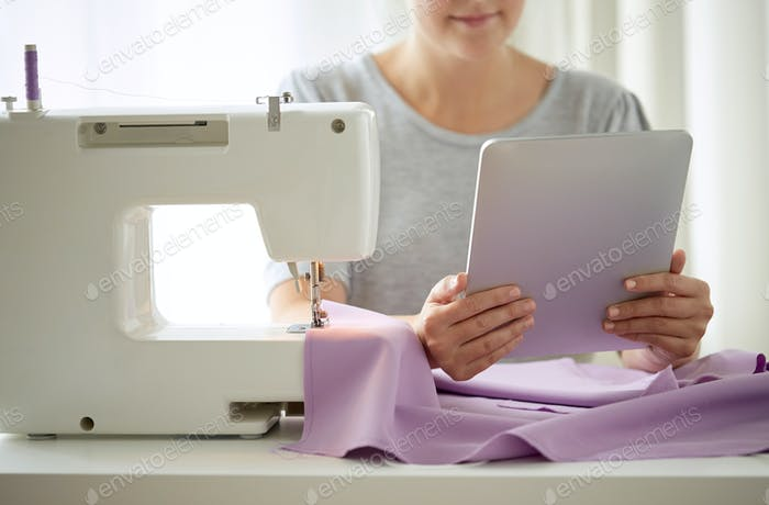 tailor with sewing machine, tablet pc and fabric