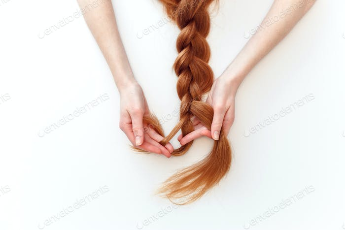 Woman with red hair braids a pigtail isolated on white background.