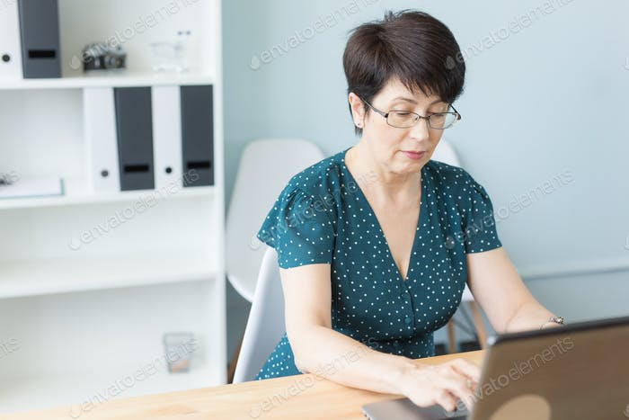 Business people and technology concept - Middle aged business woman working on laptop in her office