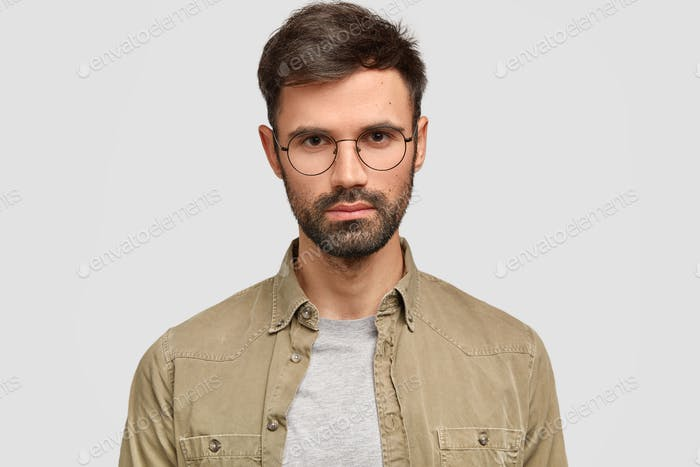 Headshot of handsome bearded serious young male freelancer with appealing appearance, looks directly