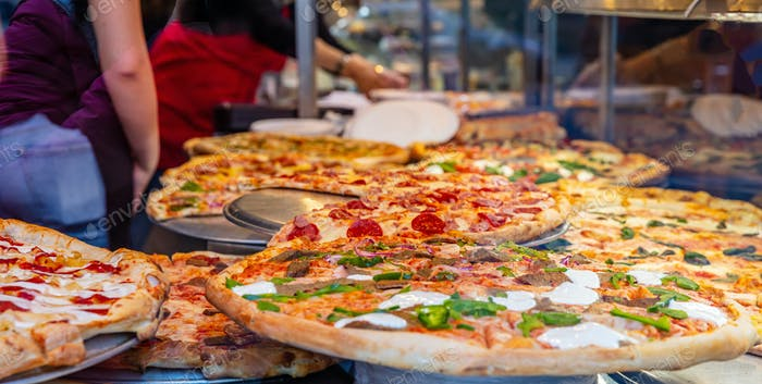 Sortiment italienischer Pizzen im Shop-Display. Weibliche Arbeiter, die die Pizzen servieren.