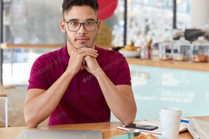 Indoor shot of mixed race man keeps hands under chin, looks with self confident facial expression, w