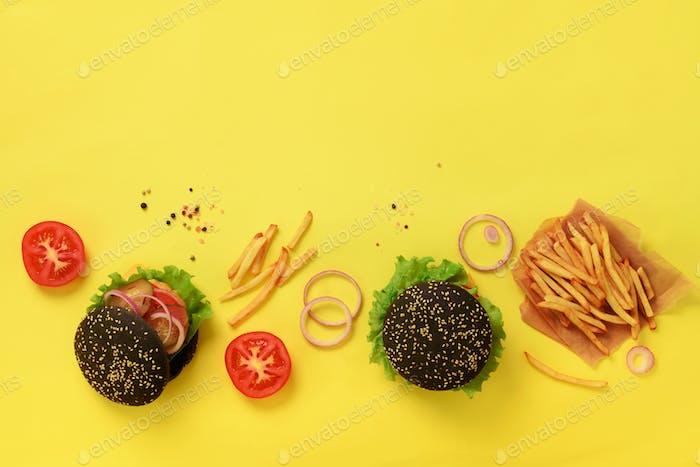 Schwarze Burger mit Rindfleisch, Tomaten, Käse, Zwiebeln, Gurken und Salat auf gelbem Hintergrund. Ansicht von oben