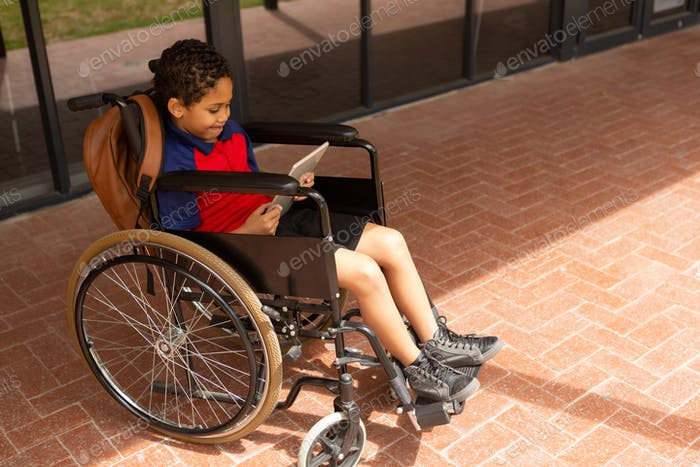 Disabled schoolboy using digital tablet in corridor at elementary school